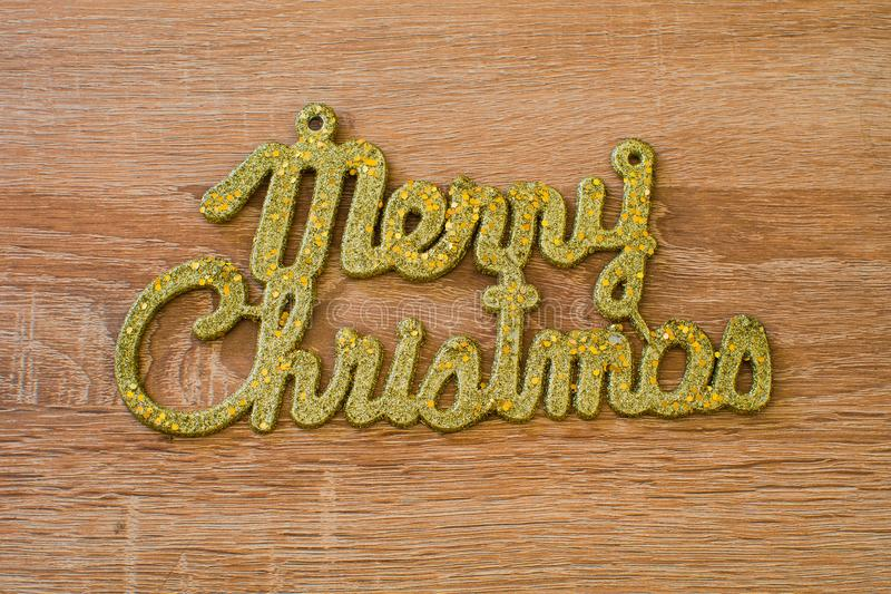 Merry Christmas golden text on a wooden background royalty free stock photos
