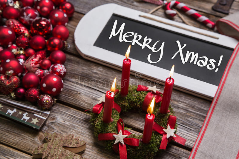 Merry christmas greeting card with four burning red candles. Merry christmas greeting card with four burning red candles and text on wooden sign royalty free stock image