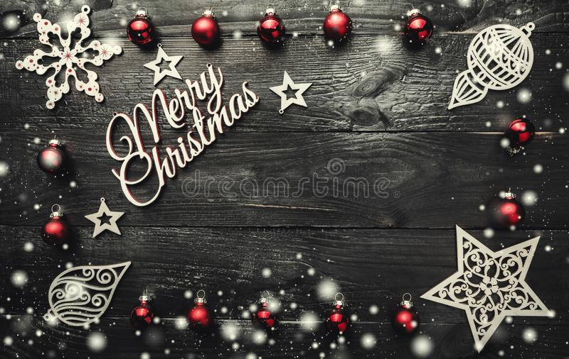 Merry Christmas greeting card with space for text. Christmas baubles, ornamented wooden toys. And snow effect on a dark wooden background royalty free stock images