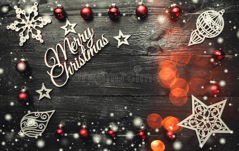 Merry Christmas greeting card. Xmas baubles, ornamented wooden toys and snowflakes. Bokeh effect on a dark background royalty free stock photos