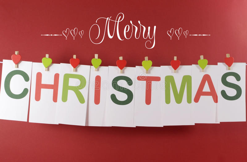 Merry Christmas greeting message across red and green letter cards hanging from heart shape pegs on a line bunting. With text against a festive red background royalty free stock images