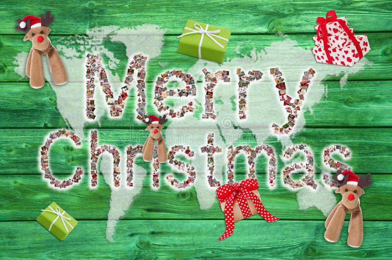 Merry christmas greetings with text on green wooden background - royalty free stock image