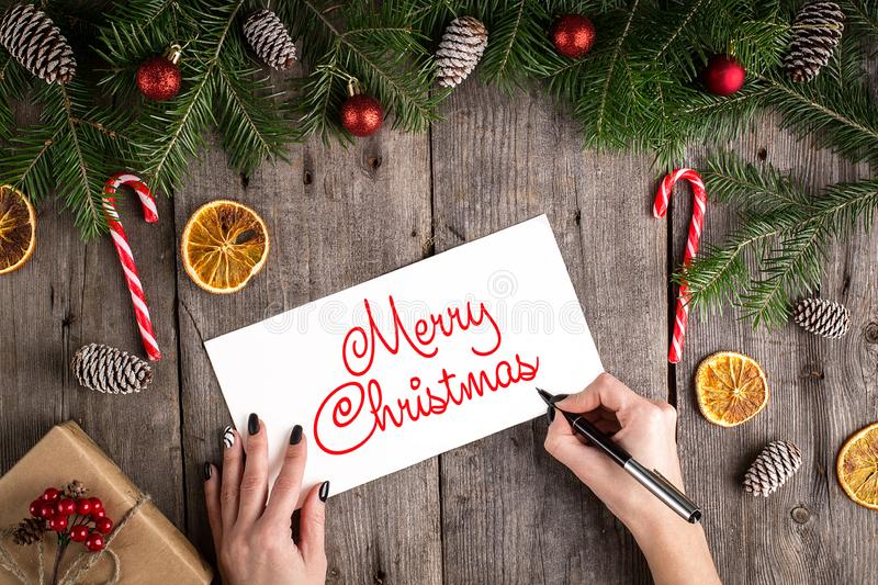 Merry Christmas hand lettering inscription on old wooden background. Pine branches and cones frame. New Year and Christmas stock image