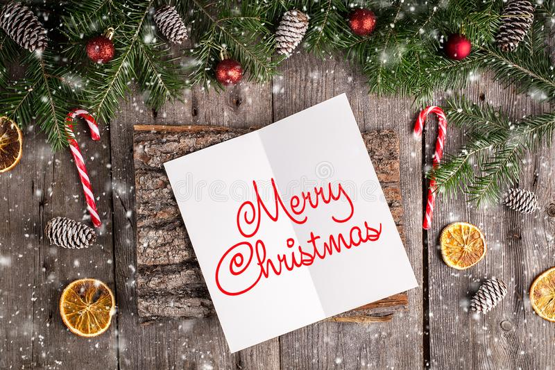 Merry Christmas hand lettering inscription on old wooden background. Pine branches and cones frame. New Year and Christmas royalty free stock images