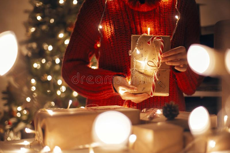merry christmas. hands holding christmas present in lights in evening festive room under tree illumination. copy space. girl open royalty free stock photos