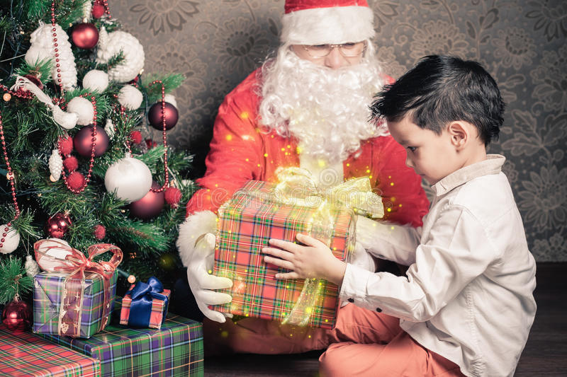 Merry Christmas! Happy boy and Santa Claus with gift box. Merry Christmas! Happy multiraceal boy shocked, surprised. Santa Claus with big gift box! Christmas stock image