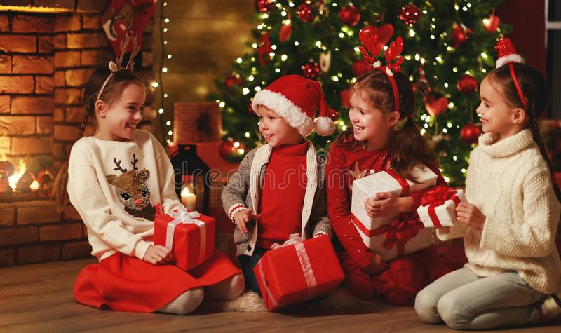 Merry Christmas! happy children with    gifts  at evening home stock images