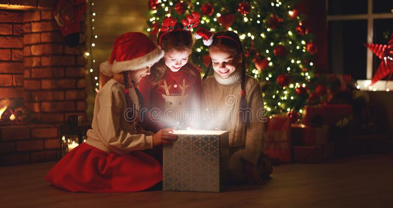 Merry Christmas! happy children with magic  gift  at evening home stock photography