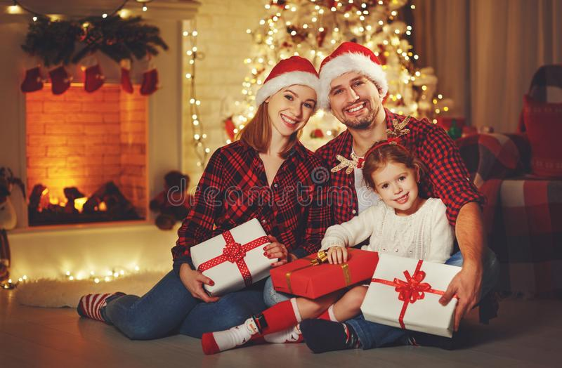 Merry Christmas! happy family mother father and child with magic. Gift near tree stock image