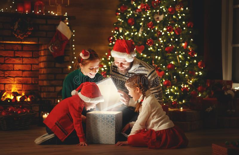 Merry Christmas! happy family mother father and children with magic gift near tree   at home royalty free stock image