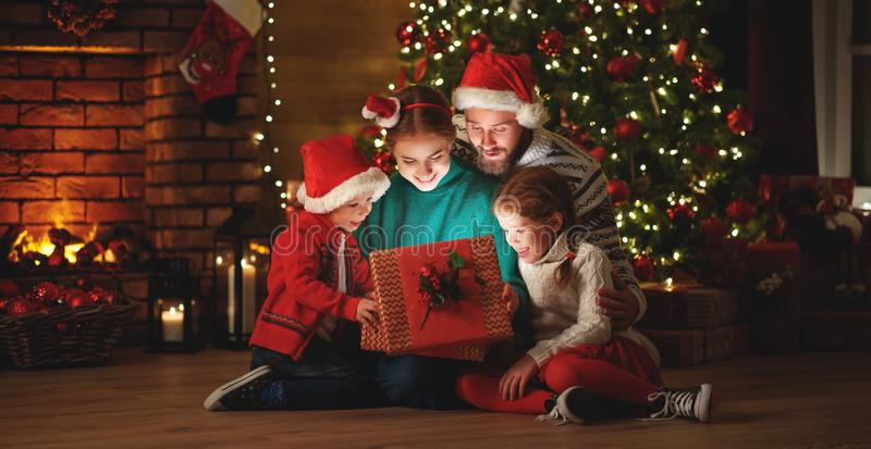 Merry Christmas! happy family mother father and children with magic gift near tree   at home stock photo