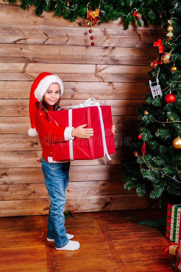 Merry Christmas and Happy Holiday. Cute little child girl with big red present gift box near tree indoor royalty free stock photos