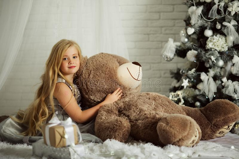Merry Christmas and Happy Holiday. Pretty blonde girl with long hair is holding big teddy bear. Merry Christmas and Happy Holiday. Pretty cute blonde girl with stock images