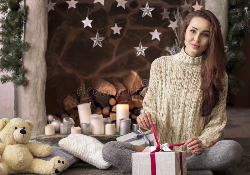 Merry Christmas and Happy Holidays! The beautiful girl is sitting next to the fireplace in the plaid opens gift. stock images