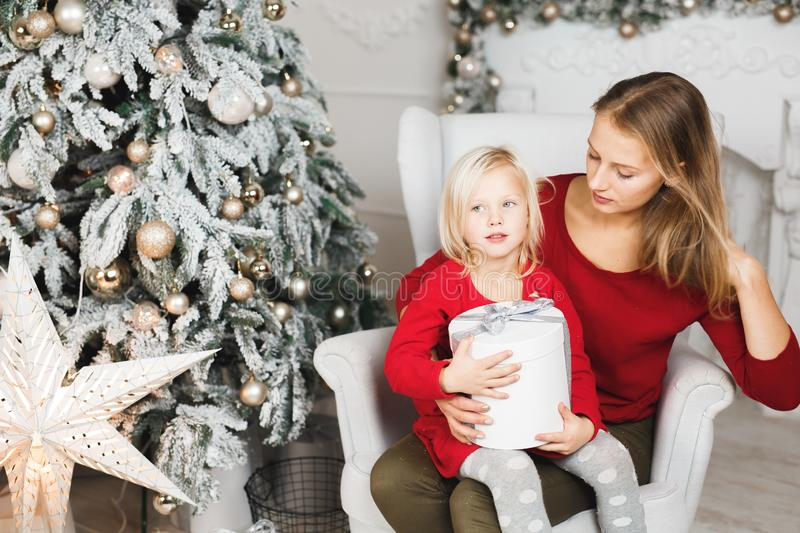 Merry Christmas and Happy Holidays. Cheerful mom and her cute daughter girl exchanging gifts stock image