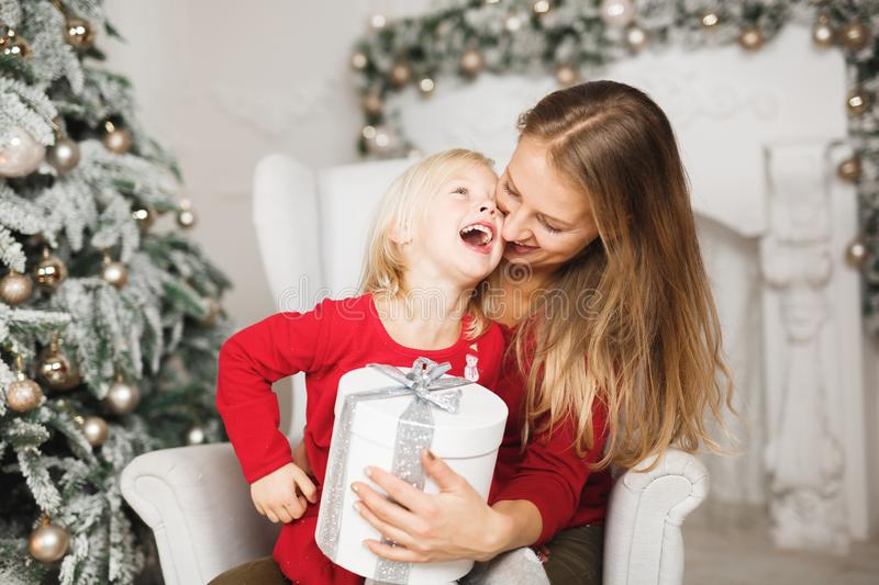 Merry Christmas and Happy Holidays. Cheerful mom and her cute daughter girl exchanging gifts stock photo