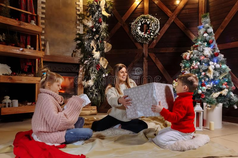 Merry Christmas and Happy New Year. Cheerful mom and her cute daughter and son exchanging gifts. Parent and children stock images