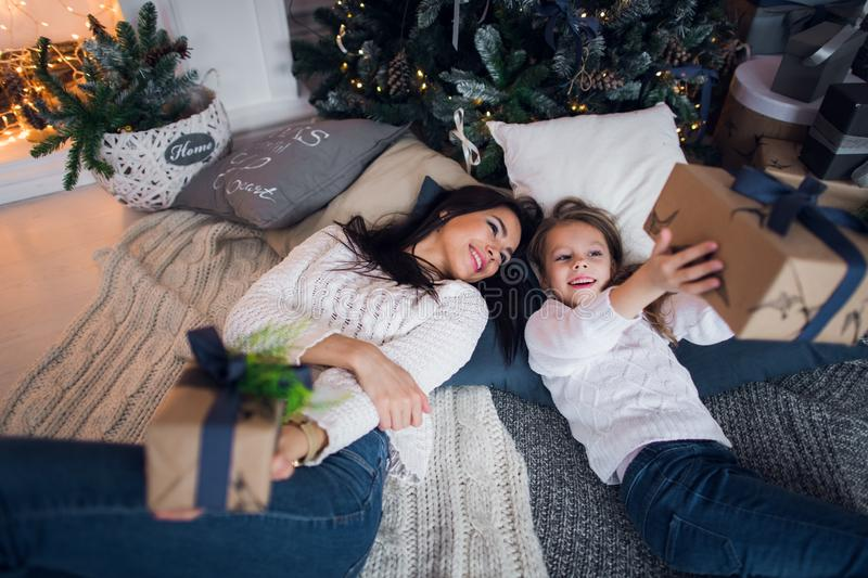 Merry Christmas and Happy Holidays. Cheerful mom and her cute daughter girl exchanging gifts. Parent and little child stock images
