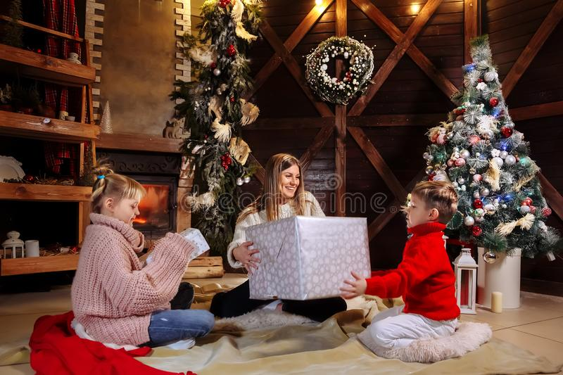 Merry Christmas and Happy New Year. Cheerful mom and her cute daughter and son exchanging gifts. Parent and children royalty free stock photo