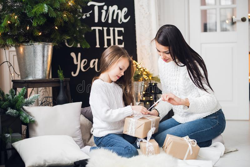 Merry Christmas and Happy Holidays. Cheerful mom and her cute daughter girl exchanging gifts. Parent and little child stock photography