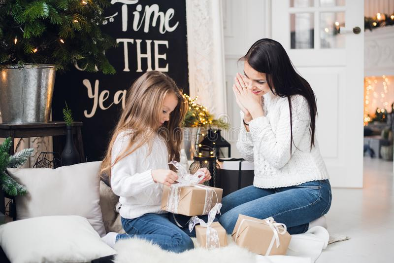 Merry Christmas and Happy Holidays. Cheerful mom and her cute daughter girl opening a Christmas present. Parent and stock image
