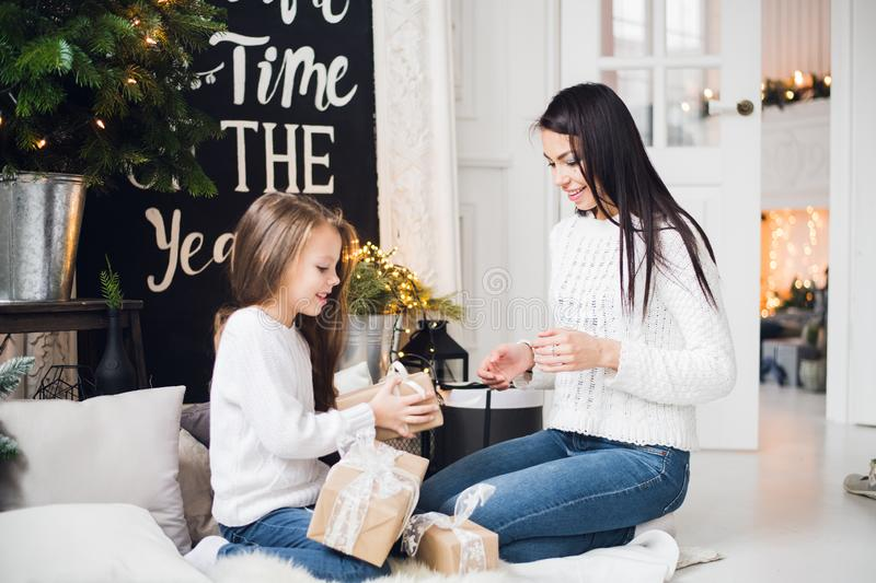 Merry Christmas and Happy Holidays. Cheerful mom and her cute daughter girl opening a Christmas present. Parent and royalty free stock images