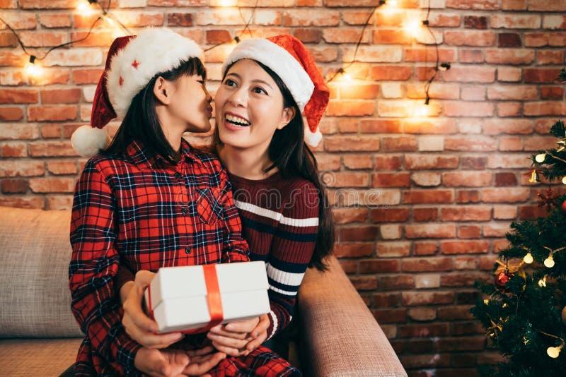 Lovely daughter in santa hat kissing mother stock image