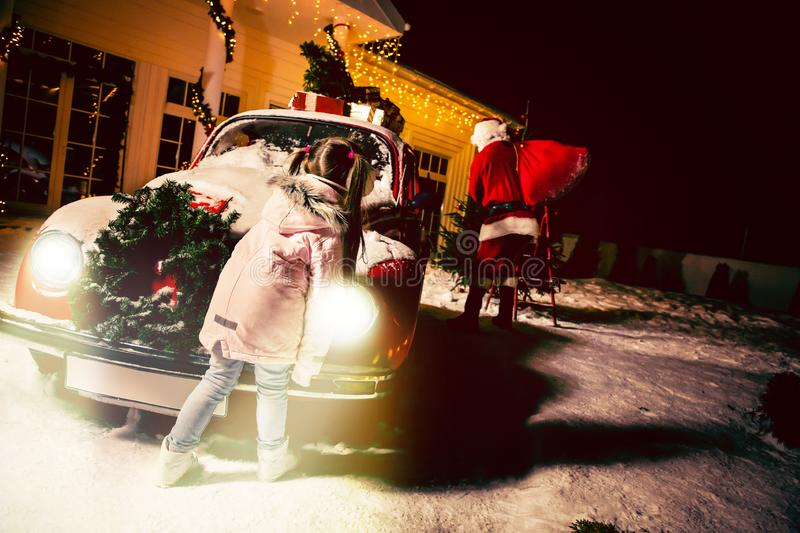 Merry Christmas and happy holidays! Cute little child girl waiting for Santa Claus. Kid enjoy the holiday royalty free stock image