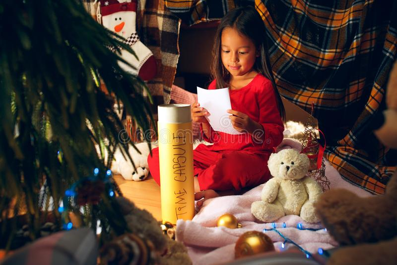 Merry Christmas and Happy Holidays. Cute little child girl writes the letter to Santa Claus near Christmas tree royalty free stock image