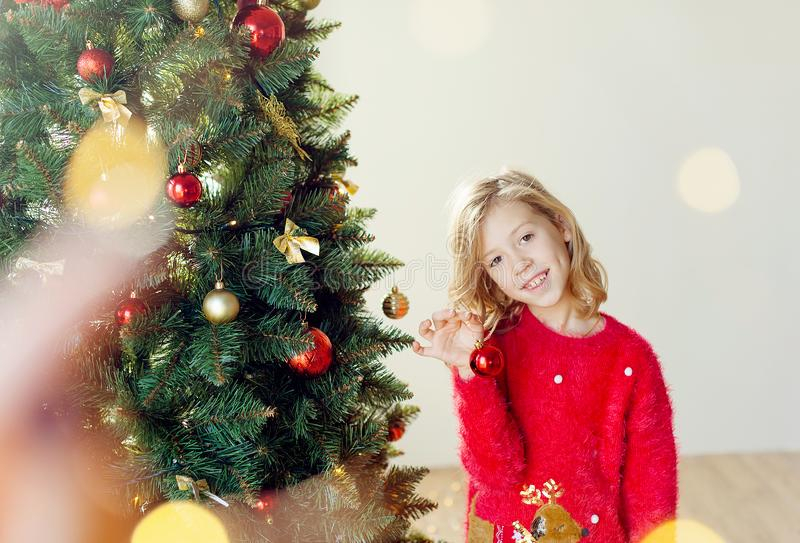 Merry Christmas and happy holidays! Cute little child girl with xmas present. Merry Christmas! Children play near the Christmas tree. Give for New Year`s gifts royalty free stock photos