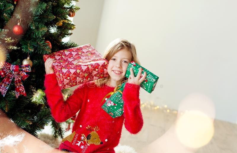 Merry Christmas and happy holidays! Cute little child girl with xmas present. Merry Christmas! Children play near the Christmas tree. Give for New Year`s gifts stock photo