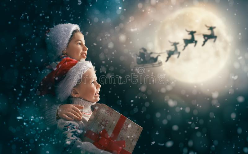 Children with xmas presents. Merry Christmas and happy holidays! Cute little children with xmas presents. Santa Claus flying in his sleigh against moon sky. Kids royalty free stock photos