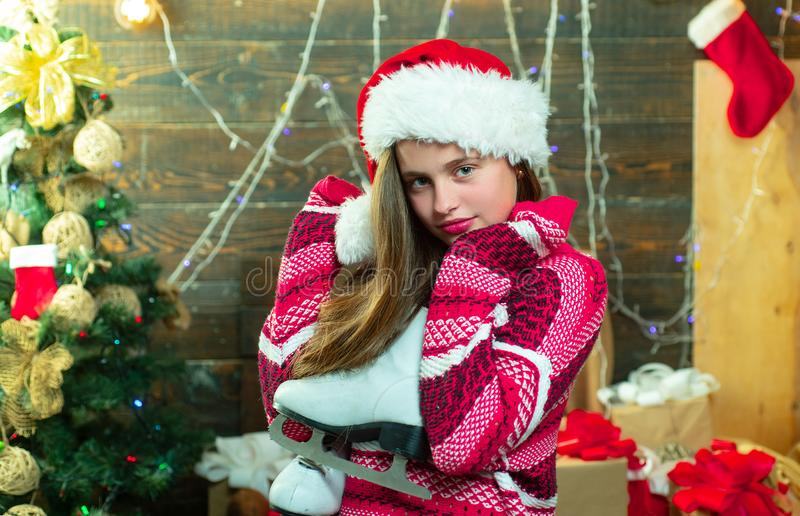 Merry Christmas and Happy Holidays. Cute little girl teenager is decorating the Christmas tree indoors. Christmas Xmas. Winter holiday concept. Merry Christmas royalty free stock photo