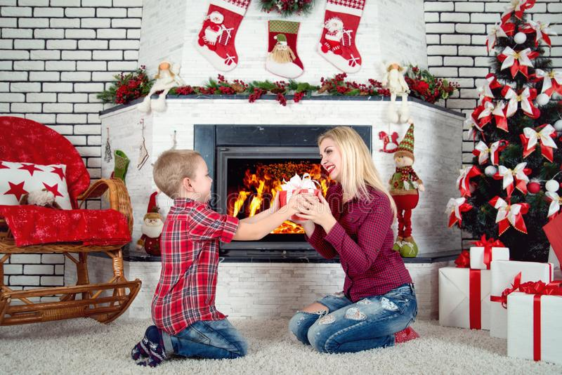 Merry Christmas and Happy Holidays!Cute son gives his beloved mother a gift.New year`s interior in the living room. royalty free stock photos