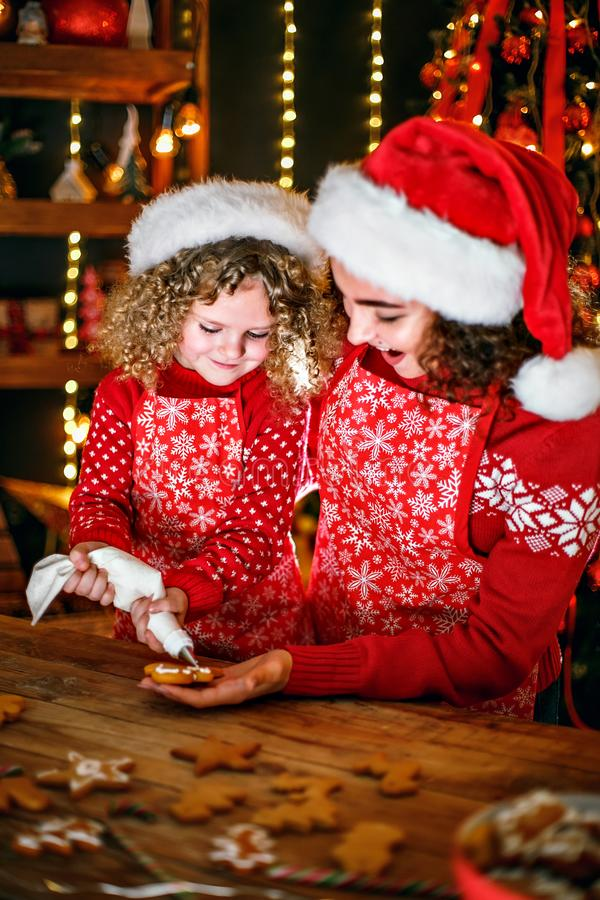 Merry Christmas and Happy Holidays. Cheerful cute curly little girl and her older sister in santas hats cooking. Merry Christmas and Happy Holidays. Family royalty free stock photo