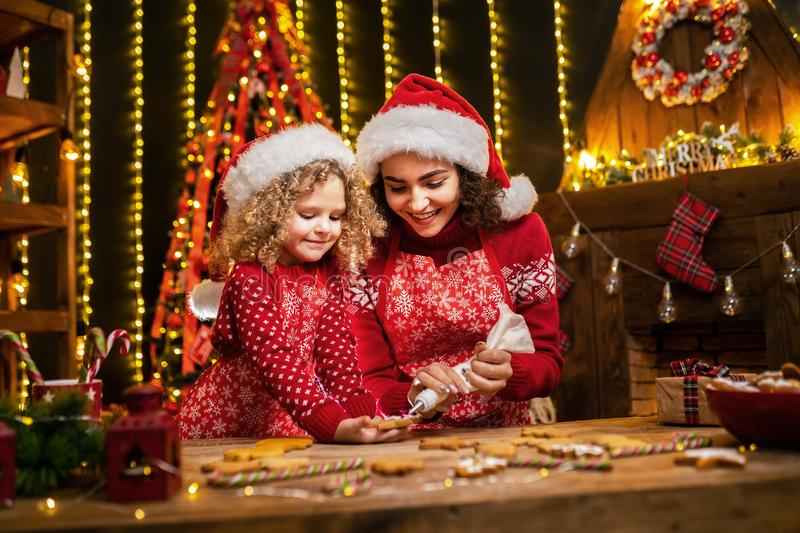 Merry Christmas and Happy Holidays. Cheerful cute curly little girl and her older sister in santas hats cooking. Merry Christmas and Happy Holidays. Family stock photo