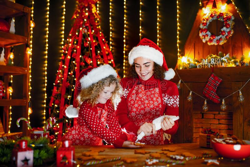 Merry Christmas and Happy Holidays. Cheerful cute curly little girl and her older sister in santas hats cooking. Merry Christmas and Happy Holidays. Family stock photos