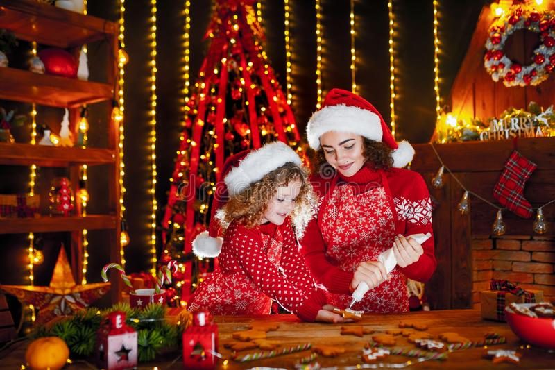 Merry Christmas and Happy Holidays. Cheerful cute curly little girl and her older sister in santas hats cooking. Merry Christmas and Happy Holidays. Family royalty free stock image