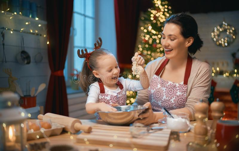Cooking Christmas cookies. Merry Christmas and Happy Holidays. Family preparation holiday food. Mother and daughter cooking cookies stock photography
