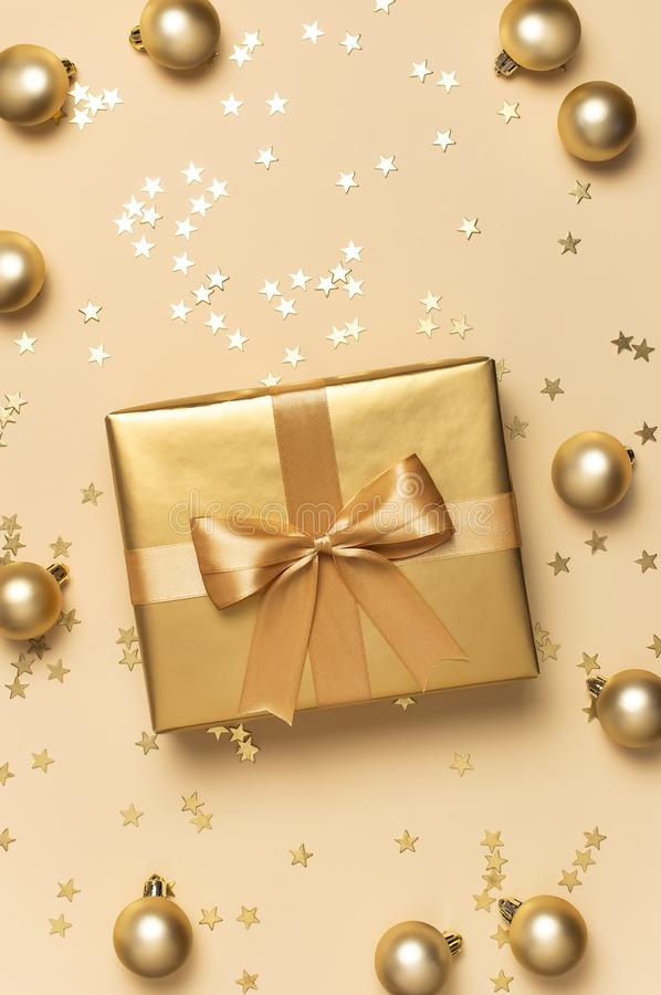Merry Christmas and Happy Holidays greeting card. Beautiful golden gift with balls and confetti stars on gold background royalty free stock photography