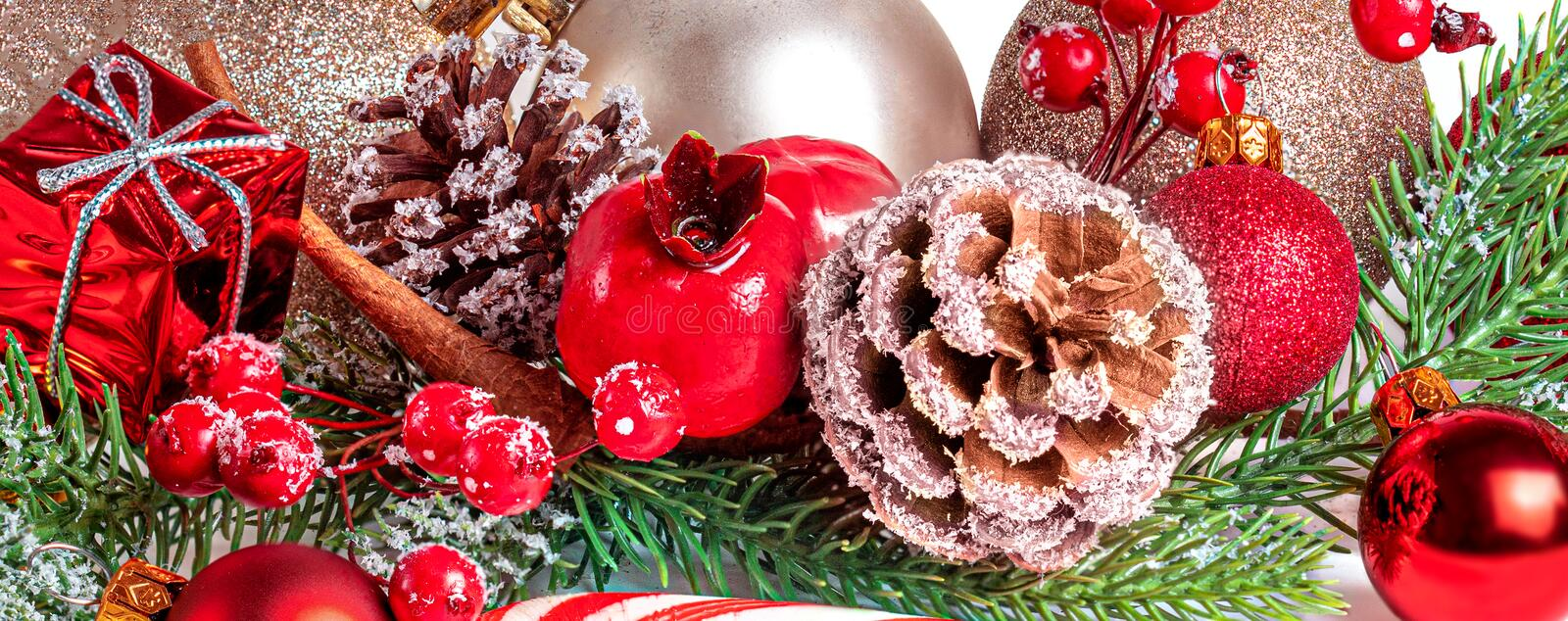 Merry Christmas and Happy Holidays greeting card.  Christmas composition with red ball, fir tree and pine cones. Winter holiday. Theme stock photo