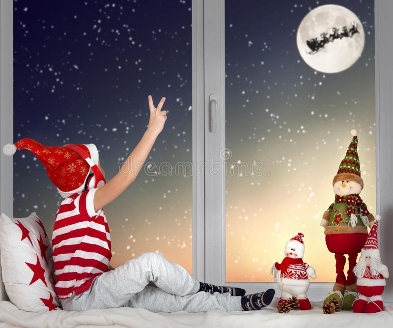 Merry Christmas .boy sitting on the window and looking at Santa Claus flying in his sleigh against moon sky. Little child boy sitting on the window and looking stock images
