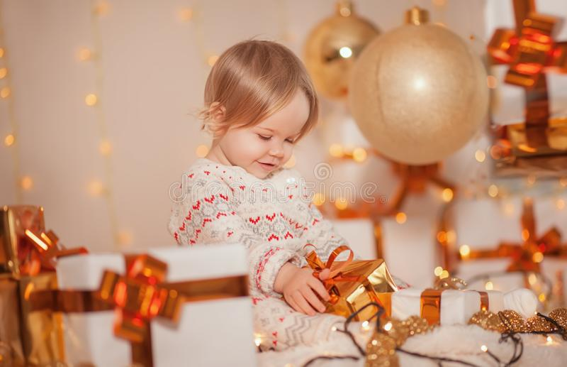 Merry Christmas and Happy Holidays! Little cute kid girl sitting in decorated room holding present box with surprise and smiling. stock image