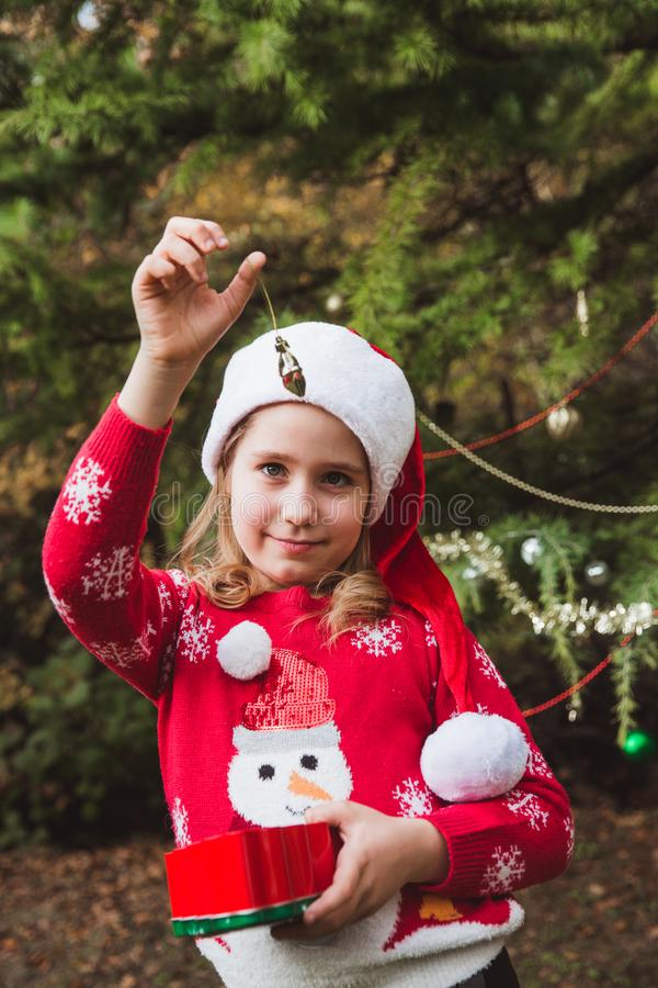 Merry Christmas and Happy Holidays. little girl decorating the Christmas tree outdoor in the yard of the house before stock photography