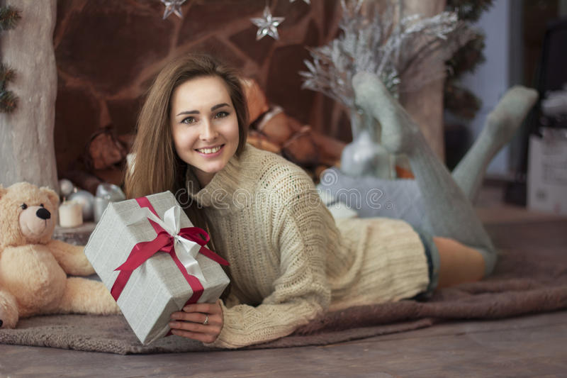 Merry Christmas and Happy Holidays! Merry girl lying near the fireplace in the blanket and holding a gift. stock photos