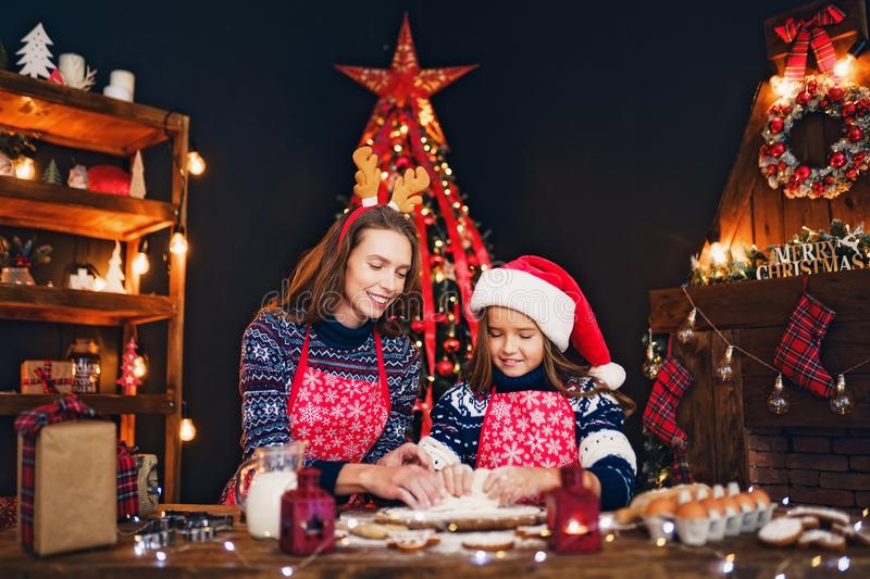 Merry Christmas and Happy Holidays. Mother and daughter cooking Christmas cookies. stock photos