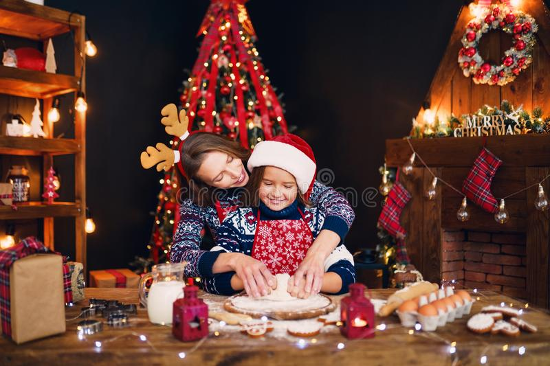 Merry Christmas and Happy Holidays. Mother and daughter cooking Christmas cookies. royalty free stock photos