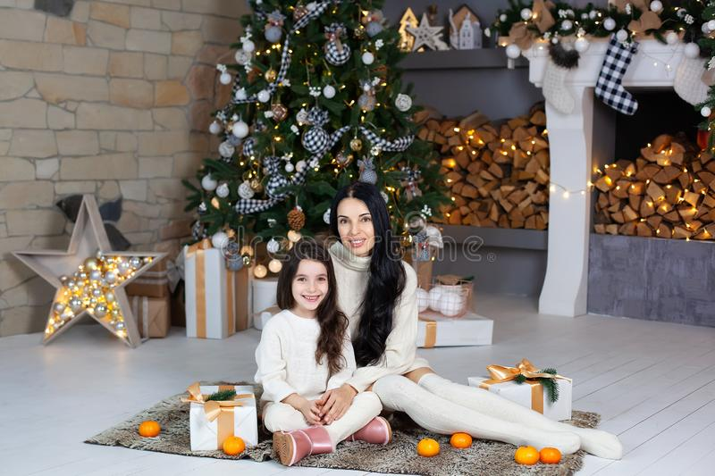 Merry Christmas and happy holidays! mother and her sweet daughter exchange gifts in living room. Parent and little child having fu stock image