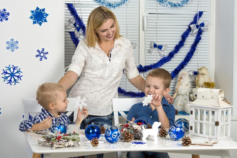 Merry Christmas and happy holidays!Mother and two sons painting a snowflake.Family creates decorations for Christmas interior. stock image