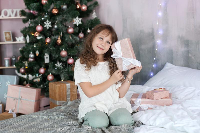 Merry Christmas and happy holidays! New Year 2020! Children, family and childhood and holiday concept. Girl in pajamas holds a New royalty free stock image